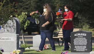 Lori Gonzalez, left, and Rachel Spray carry flowers to the temporary grave marker of Gonzalez's sister and Kaiser Permanente Fresno Medical Center nurse, Sandra Oldfield, at the Sanger Cemetery in Sanger, Calif., Saturday, Aug. 29, 2020. Oldfield died after being exposed to the novel coronavirus. Workers at the hospital said they did not have the proper personal protective equipment. (AP Photo/Gary Kazanjian)