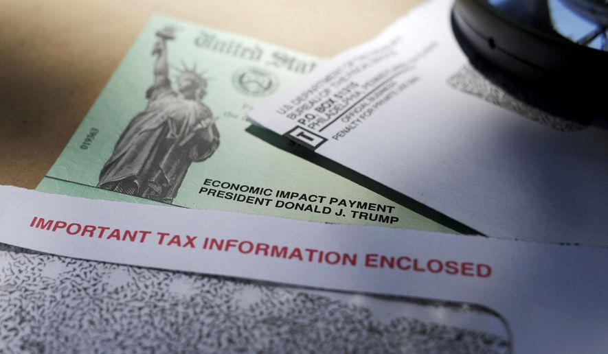 FILE - In this April 23, 2020, file photo, President Donald Trump's name is seen on a stimulus check issued by the IRS to help combat the adverse economic effects of the COVID-19 outbreak, in San Antonio, Texas. A federal judge says the IRS can't keep withholding coronavirus relief payments from incarcerated people, potentially clearing the way for at least 80,000 checks totaling more than $100 million to be sent to people behind bars across the United States. The ruling from U.S. District Judge Phyllis J. Hamilton late last month gives the IRS until Oct. 24 to reconsider the payments for those who were denied or had their money intercepted solely because of their incarceration. (AP Photo/Eric Gay, File)