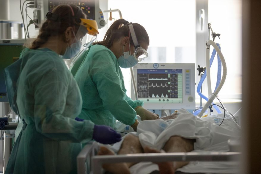 Healthcare workers assist a COVID-19 patient at one of the intensive care units (ICU) at the University Hospital of Torrejon in Torrejon de Ardoz, Spain, Tuesday, Oct. 6, 2020. Hospitals and their workers have been stretched to their limits again in Madrid, Europe's darkest spot in the second wave of the pandemic and where a second wave once again critical care beds have expanded to gymnasiums and surgery rooms. (AP Photo/Manu Fernandez)