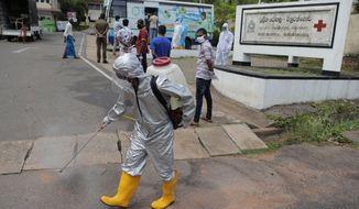 A Sri Lankan health worker sprays disinfectants as people wait to give swab samples to test for COVID-19 near a mobile testing vehicle outside a hospital in Minuwangoda, Sri Lanka, Tuesday, Oct. 6, 2020. (AP Photo/Eranga Jayawardena)