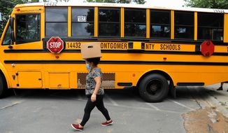 A woman walks with a box of produce she received during a food drive from bus drivers with the Montgomery County School District, Friday, July 10, 2020, in Silver Spring, Md. (AP Photo/Julio Cortez) ** FILE **