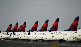 In this April 1, 2020, file photo, several dozen mothballed Delta Air Lines jets are parked at Kansas City International Airport in Kansas City, Mo. (AP Photo/Charlie Riedel, File)