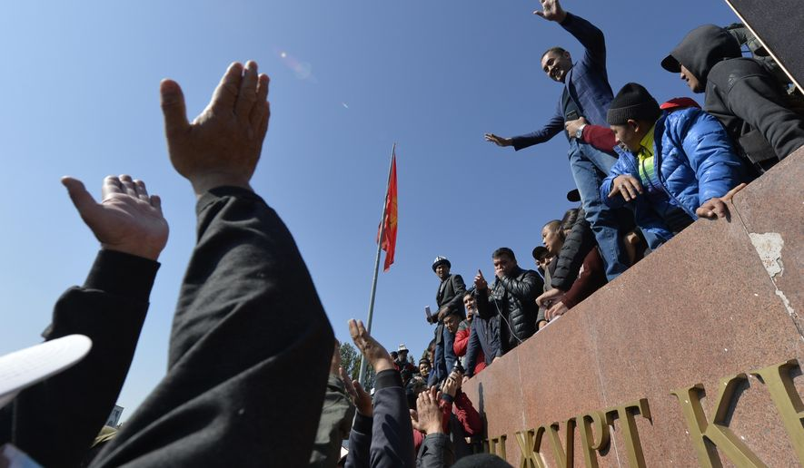 People protest during a rally on the central square in Bishkek, Kyrgyzstan, Wednesday, Oct. 7, 2020. Officials in Kyrgyzstan have nullified the results of a weekend parliamentary election after mass protests erupted in the capital of Bishkek and other cities, with opposition supporters seizing government buildings and demanding a new vote. (AP Photo/Vladimir Voronin)