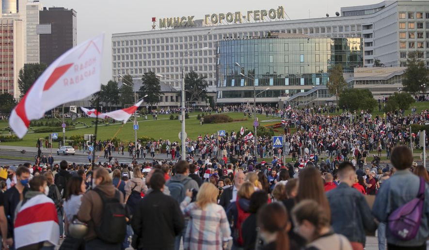People with old Belarusian national flags gather during an opposition rally to protest the presidential inauguration in Minsk, Belarus, Wednesday, Sept. 23, 2020. Belarus President Alexander Lukashenko has been sworn in to his sixth term in office at an inaugural ceremony that was not announced in advance amid weeks of huge protests saying the authoritarian leader's reelection was rigged. Hundreds took to the streets in several cities in the evening to protest the inauguration. (AP Photo/TUT.by)