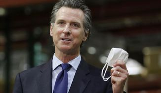 FILE - In this June 26, 2020 file photo, Gov. Gavin Newsom holds a face mask as he urges people to wear them to fight the spread of the coronavirus during a news conference in Rancho Cordova, Calif. A member of Newsom's office staff tested positive for COVID-19 this week and contact tracing has begun, the office said in a statement Wednesday, Oct. 7, 2020. The staff member had not interacted with Newsom or with staff that routinely interacts with the governor, the statement said. Separately, a state employee who works in a space shared with some staff from the governor's office also tested positive for COVID-19 but the person also had not interacted with the governor or his close staff, the office said. (AP Photo/Rich Pedroncelli, Pool, File)