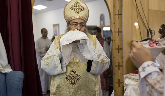 In this Sunday, Aug. 18, 2013 photo, Father Reweis Khalil brings the bread (Body of Christ) to worshippers during Sunday service at St. George Coptic Orthodox Church in Hampton, VA., on Sunday, Aug. 18, 2013. Khalil was removed from the priesthood in July. Sally Zakhari has alleged, including in a police report and to Coptic Church officials, that Khalil has sexually abused her. Khalil has denied the allegations through his attorney. (The' N. Pham/The Virginian-Pilot via AP)