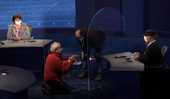 Members of the production crew stand in on the stage near plexiglass barriers which will serve as a way to protect the spread of COVID-19 as preparations take place for the vice presidential debate at the University of Utah, Tuesday, Oct. 6, 2020, in Salt Lake City. The vice presidential debate between Vice President Mike Pence and Democratic vice presidential candidate Sen. Kamala Harris, D-Calif., is scheduled for Oct. 7.  (AP Photo/Julio Cortez)