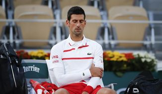 Serbia's Novak Djokovic massages his left upper arm in the quarterfinal match of the French Open tennis tournament against Spain's Pablo Carreno Busta at the Roland Garros stadium in Paris, France, Wednesday, Oct. 7, 2020. (AP Photo/Christophe Ena)