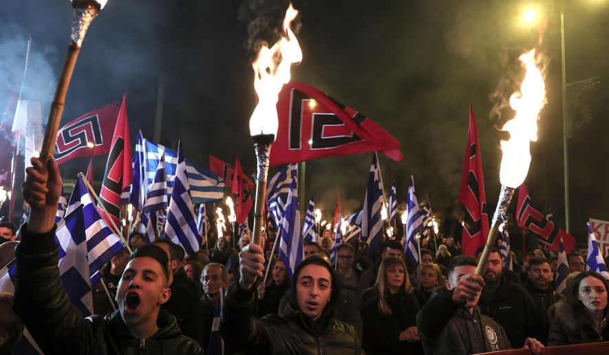FILE - In this Saturday, Feb. 2, 2019 file photo, supporters of Greece's extreme right Golden Dawn raise torches during a rally commemorating a 1996 military incident which cost the lives of three Greek navy officers and brought Greece and Turkey to the brink of war, in Athens. Greek police officials they are planning to deploy about 2,000 officers around Athens as the leadership of the extreme right group Golden Dawn faces a landmark criminal trial verdict. Eighteen former lawmakers from the party founded in the 1980s as a neo-Nazi organization are among 69 defendants who have been on trial for the past five years. The verdict is expected Wednesday Oct. 7, 2020. (AP Photo/Yorgos Karahalis, File)