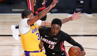 Miami Heat forward Bam Adebayo, right, drives around Los Angeles Lakers forward Anthony Davis during the first half in Game 4 of basketball's NBA Finals Tuesday, Oct. 6, 2020, in Lake Buena Vista, Fla. (AP Photo/John Raoux)