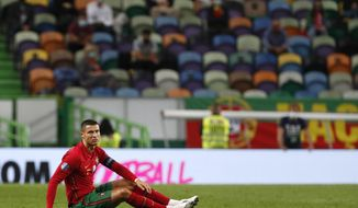Portugal's Cristiano Ronaldo, right, sits on the pitch during the international friendly soccer match between Portugal and Spain at the Jose Alvalade stadium in Lisbon, Wednesday, Oct. 7, 2020. (AP Photo/Armando Franca)