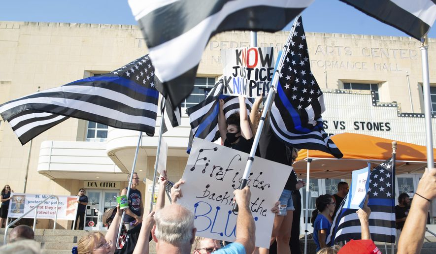 Flags and signs from Back the Blue supports cover two Black Lives Matter supporters standing in front of the Topeka, Kan., Performing Arts Center on Aug. 25, 2020, as both groups held rallies. Some advocates in Topeka see long-standing tensions between the police and the city's 125,000 residents, particularly minorities.  But advocates of change have been met by vocal support for the police. [Evert Nelson/The Topeka Capital-Journal via AP)