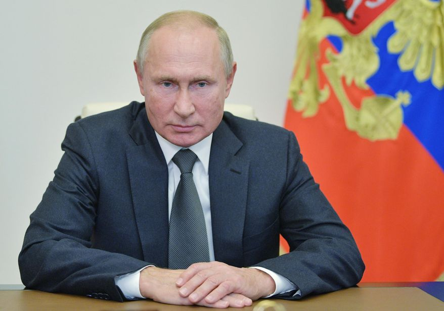 Russian President Vladimir Putin listens to General Staff chief Valery Gerasimov via a video call at the Novo-Ogaryovo residence outside Moscow, Russia, Wednesday, Oct. 7, 2020. Russian President Vladimir Putin celebrates his 68th birthday on Wednesday. (Alexei Druzhinin, Sputnik, Kremlin Pool Photo via AP)