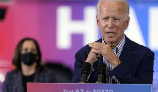 Democratic presidential candidate former Vice President Joe Biden speaks as Democratic vice presidential candidate Sen. Kamala Harris, D-Calif., listens at the Carpenters Local Union 1912 in Phoenix, Thursday, Oct. 8, 2020, to kick off a small business bus tour. (AP Photo/Carolyn Kaster)