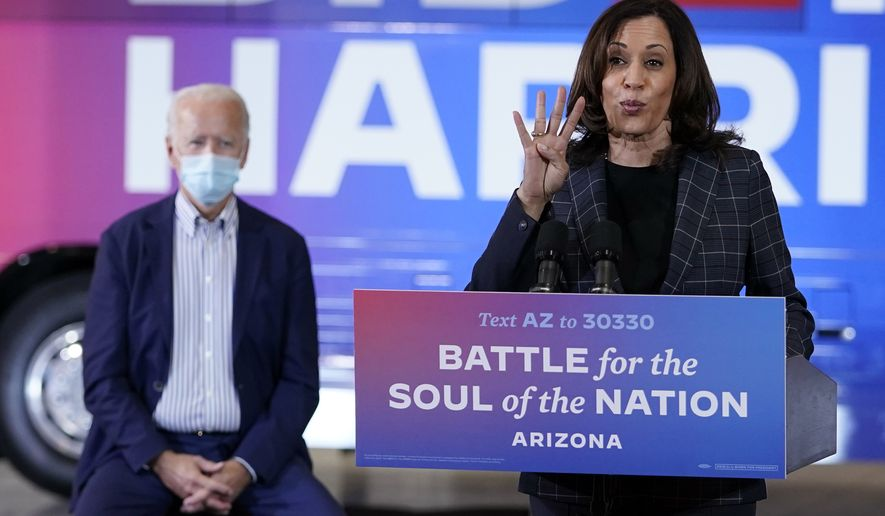 Democratic presidential candidate former Vice President Joe Biden listens as Democratic vice presidential candidate Sen. Kamala Harris, D-Calif., speaks at Carpenters Local Union 1912 in Phoenix, Thursday, Oct. 8, 2020, to kick off a small business bus tour. (AP Photo/Carolyn Kaster)