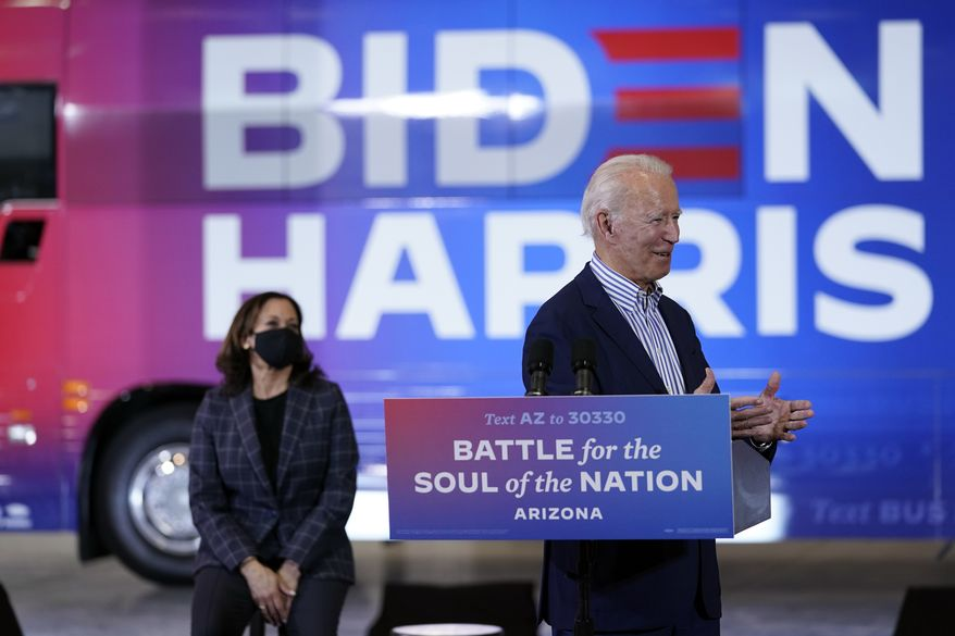 Democratic presidential candidate former Vice President Joe Biden speaks as Democratic vice presidential candidate Sen. Kamala Harris, D-Calif., listens as they visit the Carpenters Local Union 1912 in Phoenix, Thursday, Oct. 8, 2020, to kick off a small business bus tour. (AP Photo/Carolyn Kaster)