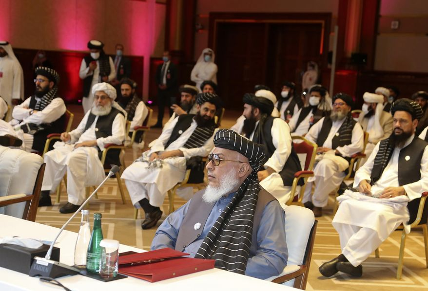 In this Sept. 12, 2020, file photo, Taliban negotiator Abbas Stanikzai, center front, and his delegation attend the opening session of peace talks between the Afghan government and the Taliban, in Doha, Qatar. Afghanistan's Taliban on Thursday, Oct. 8, 2020, welcomed a tweet from President Donald Trump in which he promised to have the last of the U.S.'s troops out of Afghanistan by Christmas. (AP Photo/Hussein Sayed, File)