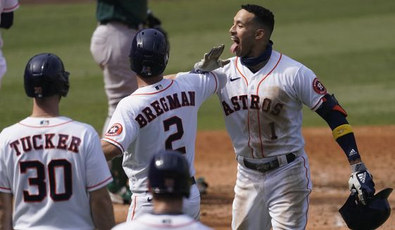Houston Astros' Carlos Correa, right, celebrates after hitting a three-run home run that scored Kyle Tucker (30) and Alex Bregman (2) during the fourth inning of Game 4 of a baseball American League Division Series against the Oakland Athletics in Los Angeles, Thursday, Oct. 8, 2020. (AP Photo/Ashley Landis)  **FILE**