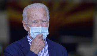 With the Arizona state flag in the background, Democratic presidential candidate former Vice President Joe Biden speaks to members of the media before leaving Phoenix Sky Harbor International Airport, in Phoenix, Thursday, Oct. 8, 2020. (AP Photo/Carolyn Kaster)
