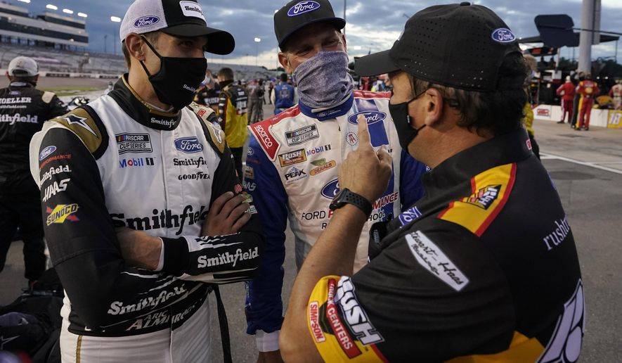 Aric Almirola, left, and Clint Bowyer, center, talks to a crew member prior to the start of a NASCAR Cup Series auto race Saturday, Sept. 12, 2020, in Richmond, Va. (AP Photo/Steve Helber)