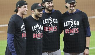 Atlanta Braves starting pitchers, from left, Max Fried, catcher Travis d'Arnaud, Ian Anderson, and Kyle Wright pose as the Braves celebrate advancing to the NL Championship Series by defeating the Marlins 7-0 in Game 3 of a Division Series, Thursday, Oct. 8, 2020, in Houston. (Curtis Compton/Atlanta Journal-Constitution via AP)