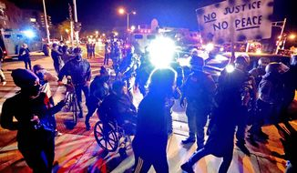 Protesters march in Wauwatosa, Wis., around a line of National Guardsmen protecting the Wauwautosa City Hall, late Wednesday, Oct. 7, 2020. Earlier, District Attorney John Chisolm refused to issue charges against Wauwatosa Police Officer Joseph Mensah for the Feb. 2 fatal shooting of 17-year-old Alvin Cole at Mayfair Mall. Protests and possibly violence are expected after the decision has prompted Wauwatosa officials to shut down City Hall for about three days, beginning at noon Wednesday. (Rick Wood/Milwaukee Journal-Sentinel via AP)