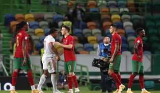 Portugal's Diogo Jota, center, shakes hands with Spain's Adama Traore after the international friendly soccer match between Portugal and Spain at the Jose Alvalade stadium in Lisbon, Wednesday, Oct. 7, 2020. (AP Photo/Armando Franca)