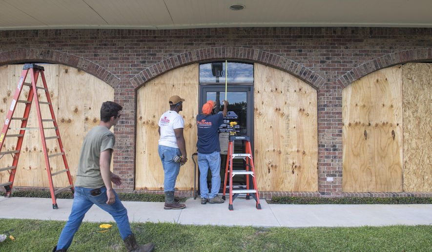 Bernie Arnould, center, gets help from Kaden Ashley and D.J. Hebert, left, all with Pelican Companies, as they board up the windows to the front of MC Bank in Amelia, La., Wednesday, Oct., 7, 2020, in In preparation for Hurricane Delta.  (Chris Granger/The Times-Picayune/The New Orleans Advocate via AP)