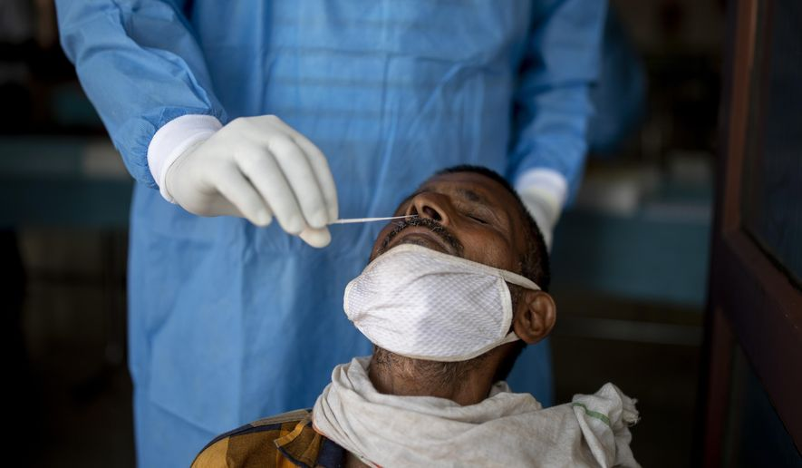 A health worker takes a nasal swab to test for COVID-19 in New Delhi, India, Thursday, Oct. 8, 2020. India is the world's second most coronavirus affected country after the United States. (AP Photo/Altaf Qadri)