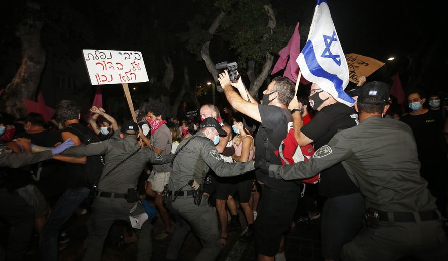 """FILE - In this Tuesday, Oct. 6, 2020 file photo, Israeli police scuffle with protesters during a demonstration against Prime Minister Benjamin Netanyahu in Tel Aviv, Israel. The Israeli government has extended an emergency provision that bars public gatherings, including widespread protests against Netanyahu, for an additional week. The sign reads """"Bibi you failed the wrong generation."""" (AP Photo/Ariel Schalit, File)"""