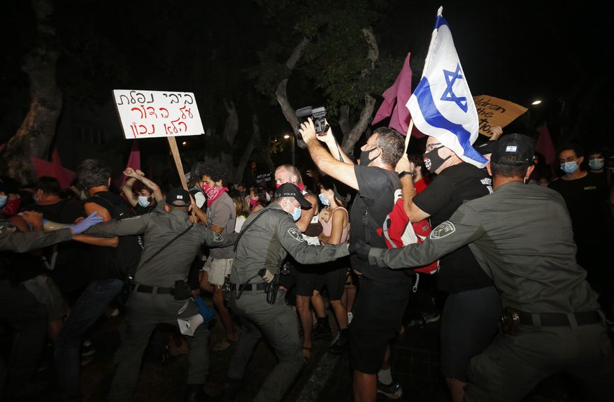 "FILE - In this Tuesday, Oct. 6, 2020 file photo, Israeli police scuffle with protesters during a demonstration against Prime Minister Benjamin Netanyahu in Tel Aviv, Israel. The Israeli government has extended an emergency provision that bars public gatherings, including widespread protests against Netanyahu, for an additional week. The sign reads ""Bibi you failed the wrong generation."" (AP Photo/Ariel Schalit, File)"