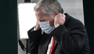 White House chief of staff Mark Meadows replaces his face covering after a television interview at the White House, Wednesday, Oct. 7, 2020, in Washington. (AP Photo/Alex Brandon)