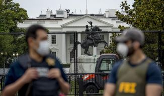 In this June 2, 2020, file photo, the White House is visible behind a large security fence as uniformed Secret Service and FBI agents stand on the street in front of Lafayette Park in the morning hours in Washington. Federal and state law enforcement officials have begun expanded preparations for the possibility of widespread unrest at the polls on Election Day, a response to extraordinarily high tensions among voters and anxieties about safety stoked in part by President Donald Trump. (AP Photo/Andrew Harnik, File)