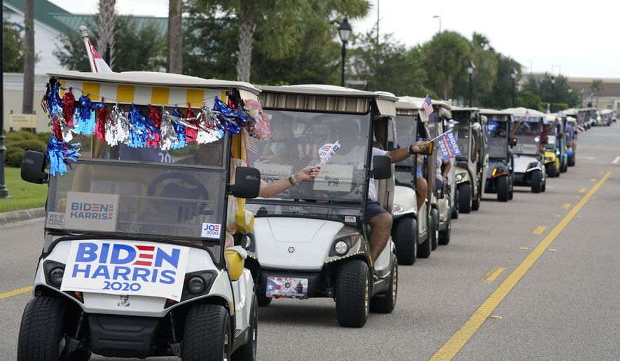 In this file photo, a parade of over 300 golf carts supporting Democratic presidential candidate former Vice President Joe Biden caravanned to the Sumter County Elections office to cast their ballots during early voting Wednesday, Oct. 7, 2020, in The Villages, Fla. (AP Photo/John Raoux)  **FILE**