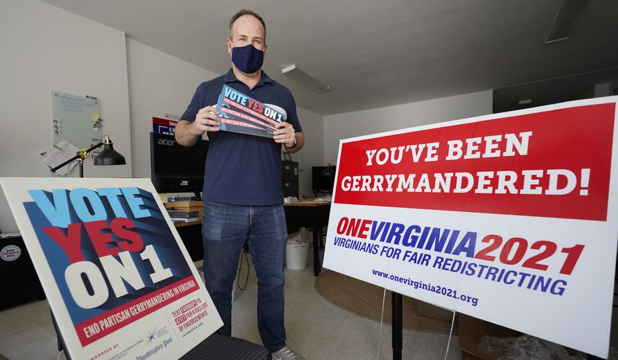 Redistricting reform advocate Brian Cannon poses with some of his yard signs and bumper stickers in his office, Tuesday, Oct. 6, 2020, in Richmond, Va. An effort to end centuries of partisan gerrymandering in Virginia is up for consideration by the state's voters. A referendum on the November ballot asks whether to amend the state Constitution to create a bipartisan panel that would take on the once-every-10-year task of redrawing the legislative boundaries for General Assembly and congressional districts  (AP Photo/Steve Helber)