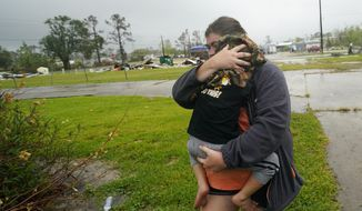 ADDS CITY - Danielle Fontenot runs to a relative's home in the rain with her son Hunter ahead of Hurricane Delta, Friday, Oct. 9, 2020, in Lake Charles, La. Forecasters said Delta — the 25th named storm of an unprecedented Atlantic hurricane season — would likely crash ashore Friday evening somewhere on southwest Louisiana's coast. (AP Photo/Gerald Herbert)
