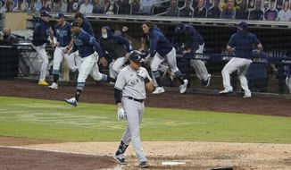 New York Yankees' Gio Urshela walks back to the dugout after flying out for the final out in Game 5 of the baseball team's AL Division Series against the Tampa Bay Rays, Friday, Oct. 9, 2020, in San Diego. Tampa Bay won 2-1 to advance. (AP Photo/Gregory Bull)