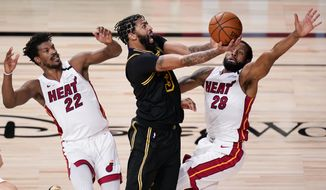 Los Angeles Lakers forward Anthony Davis shoots between Miami Heat forward Jimmy Butler, left, and guard Andre Iguodala during the second half in Game 5 of basketball's NBA Finals Friday, Oct. 9, 2020, in Lake Buena Vista, Fla. (AP Photo/John Raoux)