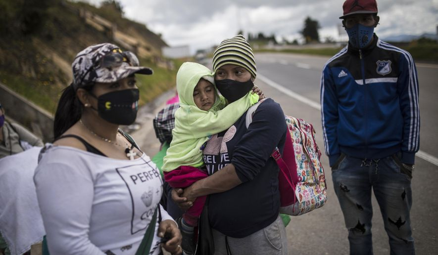 Venezuelan migrants rest as they walk towards Bogota, passing through Tunja, Colombia, Tuesday, Oct. 6, 2020. Immigration officials in Colombia expect 200,000 Venezuelans to enter the country in the following months, enticed by the prospects of earning higher wages and sending money home to feed their families.  (AP Photo/Ivan Valencia)