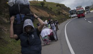 Venezuelan migrants walk to Bogota as they pass through Tunja, Colombia, Tuesday, Oct. 6, 2020. Thousands of Venezuelans are heading to Colombia, Ecuador and Peru in search of work as these countries reopen their economies following months of lockdowns. (AP Photo/Ivan Valencia)