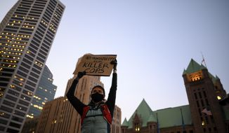 A protester holds a sign while listening to speakers outside Hennepin County Government Center in Minneapolis, Thursday, Oct. 8, 2020. Protesters took to the streets of Minneapolis on Thursday night, angry that Derek Chauvin, the former Minneapolis Police officer who faces charges of murder and other counts in the death of George Floyd in May, posted a $1 million bond Wednesday and was released. (Aaron Lavinsky/Star Tribune via AP)