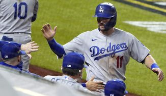 Los Angeles Dodgers' A.J. Pollock (11) is congratulated after scoring on a sacrifice fly by Mookie Betts against the San Diego Padres during the fifth inning in Game 3 of a baseball National League Division Series Thursday, Oct. 8, 2020, in Arlington, Texas. (AP Photo/Sue Ogrocki)