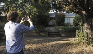 Sean Costello, of Arcadia, photographs Eddie Van Halen's childhood home, Tuesday, Oct. 6, 2020, in Pasadena, Calif. Van Halen, who had battled cancer, died Tuesday at age 65. (Richard Shotwell/Invision/AP)