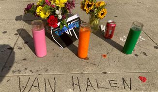 Legend has it that the name Van Halen, seen etched in concrete at the corner of Allen and Villa in Pasadena, Calif., was done by brothers Eddia and Alex Van Halen when they lived in Pasadena, Calif., in their younger years, where a sidewalk memorial has begun, Tuesday, Oct. 6, 2020, after Eddie's death earlier in the day. Artists from Lenny Kravitz to Kenny Chesney are honoring Van Halen, whose blinding speed, control and innovation propelled his band into one of hard rock's biggest groups. (AP Photo/Andrew Dalton)