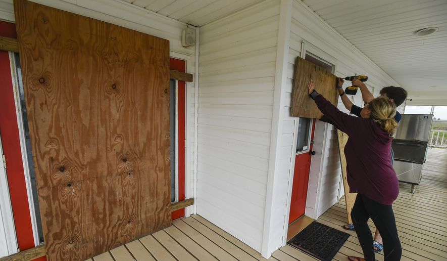 Residents Mamie Russo and her son Cole attach wood to their front door while preparing for Hurricane Delta on Thursday, Oct. 8, 2020, in Cypremort Point, La. (Brad Kemp/The Advocate via AP)