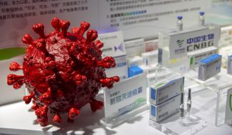 A model of a coronavirus is displayed next to boxes for COVID-19 vaccines at an exhibit by Chinese pharmaceutical firm Sinopharm at the China International Fair for Trade in Services (CIFTIS) in Beijing, Saturday, Sept. 5, 2020. China said Friday, Oct. 9, 2020, that it is joining the COVID-19 vaccine alliance known as COVAX. (AP Photo/Mark Schiefelbein)