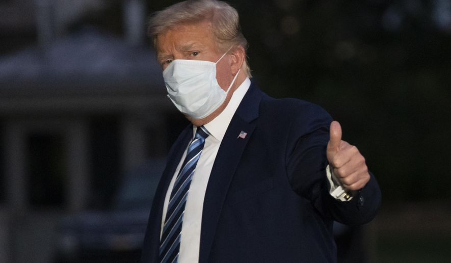 President Donald Trump gives thumbs up as he returns to the White House Monday, Oct. 5, 2020, in Washington, after leaving Walter Reed National Military Medical Center, in Bethesda, Md. Trump announced he tested positive for COVID-19 on Oct. 2. (AP Photo/Alex Brandon)