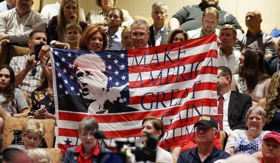 In this Thursday, Oct. 3, 2019, file photo, supporters of President Donald Trump hold a flag before he arrives to deliver remarks on Medicare at the Sharon L. Morse Performing Arts Center in The Villages, Fla. (AP Photo/Evan Vucci) ** FILE **