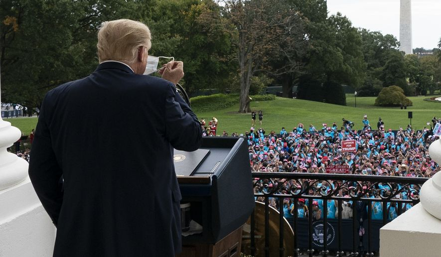 President Donald Trump removes his mask before speaking from the Blue Room Balcony of the White House to a crowd of supporters, Saturday, Oct. 10, 2020, in Washington. (AP Photo/Alex Brandon)