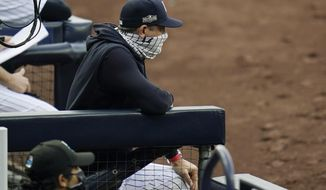 New York Yankees manager Aaron Boone wears a mask as he stands in the dugout during the third inning in Game 4 of a baseball American League Division Series against the Tampa Bay Rays, Thursday, Oct. 8, 2020, in San Diego. (AP Photo/Gregory Bull)